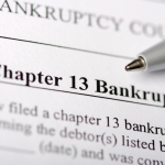 A document titles Chapter 13 Bankruptcy. A pen lays on top of the paper.